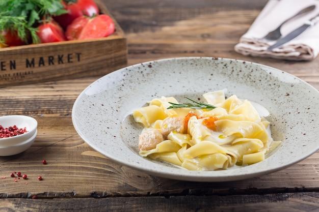 Plat traditionnel italien. pâtes au saumon servies sur assiette blanche, à l'intérieur du restaurant sur une table en bois, tomates en arrière-plan et couverts.