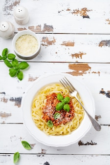 Plat traditionnel italien de pâtes fettuccine avec sauce bolognaise, basilic et parmesan dans une assiette blanche sur une surface en bois clair