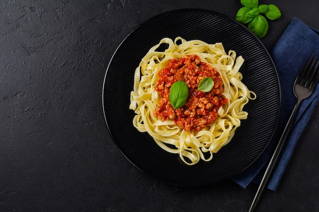 Plat traditionnel italien de pâtes fettuccine avec sauce bolognaise, basilic et parmesan en plaque noire sur une surface en bois sombre