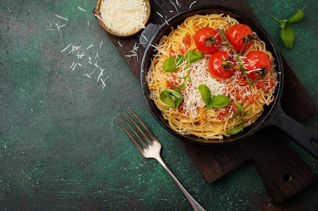 Plat traditionnel italien de spaghettis à la sauce tomate et parmesan dans une poêle en fer sur une vieille surface de béton sombre. mise au point sélective. vue de dessus.