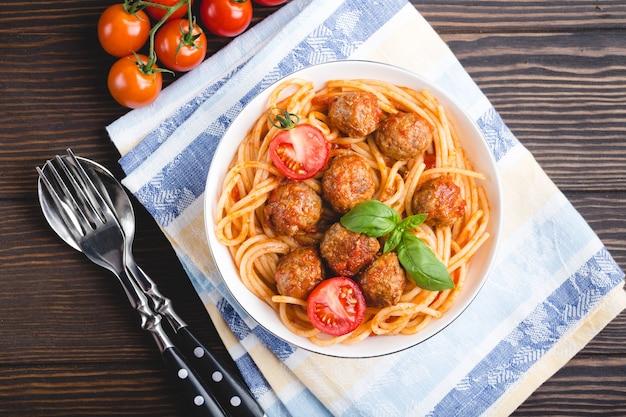 Plat traditionnel italo-américain spaghetti aux boulettes de viande, sauce tomate et basilic dans un bol, avec couverts et serviette, fond en bois rustique