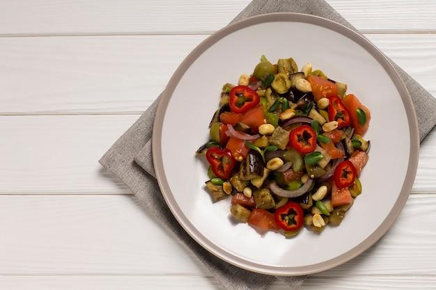 Plat traditionnel sicilien d'aubergine caponata, sur une assiette, sur une table en bois. vue de dessus