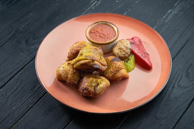 Un plat turc appétissant - kebab de cuisse de poulet aux légumes grillés et rouge, servi dans une assiette rouge