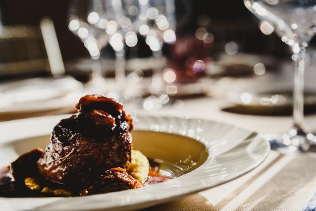 Plat de veau avec sauce servi dans des couverts de luxe