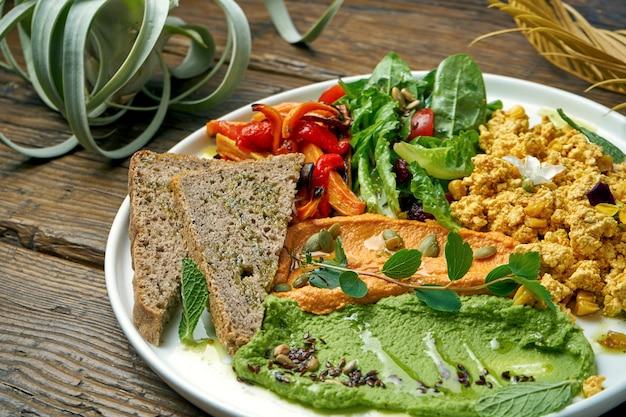 Un plat végétarien appétissant se compose de tofu, d'une salade de poivrons cuits et de roquette et de deux types de houmous. bois