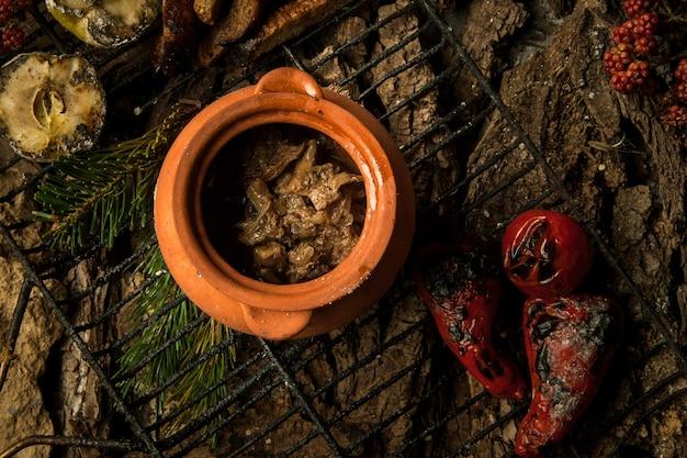 Plat végétarien dans un pot en argile avec des légumes rôtis sur le gril sur fond d'écorce d'arbre