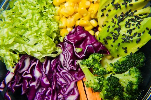 Plat végétarien, saladier. ingrédients brocoli, maïs, carottes, couscous, laitue, chou