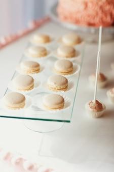 Un plat en verre avec des macarons blancs se tient sur la table