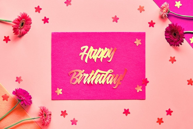 Plat vibrant poser avec des fleurs de gerbera avec texte papier joyeux anniversaire sur feutre rose.