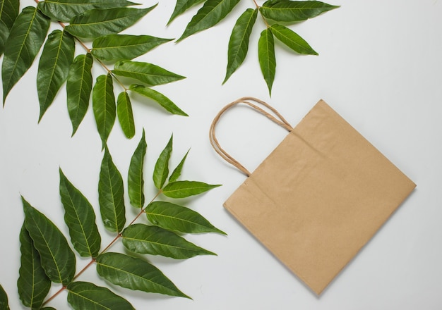 Plat la vie toujours accro au shopping. sac en papier écologique sur fond blanc parmi les feuilles vertes. vue de dessus