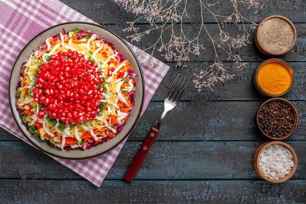 Plat vue de dessus et assiette de fourchette d'un plat appétissant sur la nappe à côté des bols de branches d'arbres d'épices et d'une fourchette sur la table grise