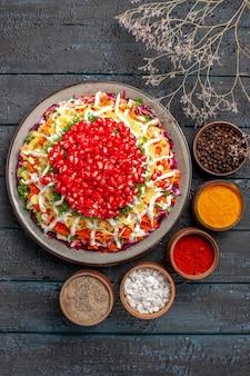 Plat vue de dessus avec des graines de grenade le plat de noël avec des graines de grenade à côté des bols d'épices colorées et de branches d'arbres sur la table