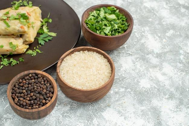 Plat de vue latérale avec assiette d'herbes de chou farci à côté du bol avec riz aux herbes et poivre noir sur la table