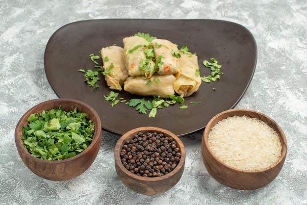 Plat de vue rapprochée latérale avec assiette d'herbes de chou farci et bols d'herbes riz papper noir sur fond gris