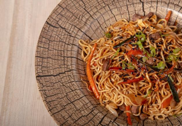 Plat de yakisoba, nouilles sautées, légumes et viande. image aérienne avec espace copie