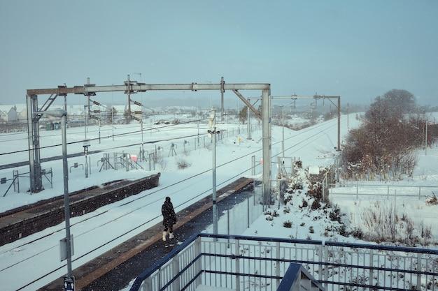 Plate-forme de la gare dans la neige et un passager solitaire marche en ecosse en hiver
