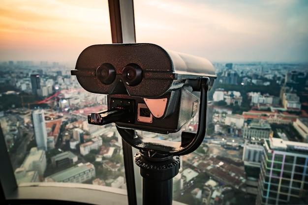 Plate-forme d'observation sur un grand bâtiment avec de grandes jumelles pour observer le magnifique panorama de saigon ou ho chi minh-ville. viêt nam.