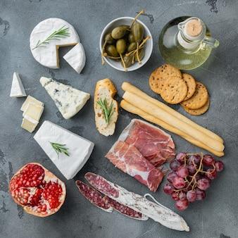 Plateau d'antipasti avec du fromage frais, du pain et des olives, sur table grise, vue du dessus