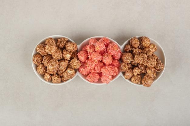 Plateau apéritif avec assortiment de bonbons pop-corn sur marbre.