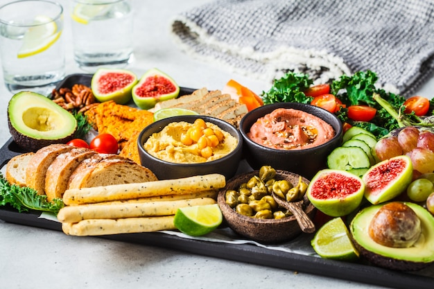 Plateau apéritif végétalien, houmous, tofu, légumes, fruits et pain