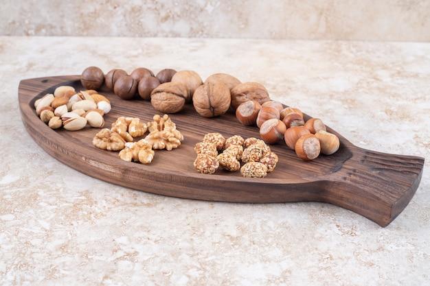 Plateau avec assortiment de noix et boules de chocolat sur marbre