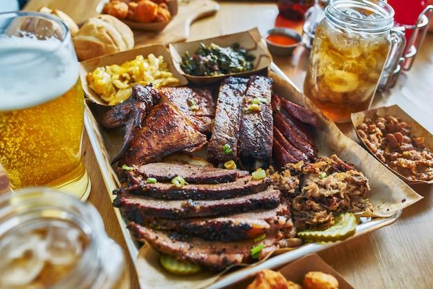 Plateau de barbecue à la texane avec poitrine fumée, porc effiloché, poulet, hot links et accompagnements