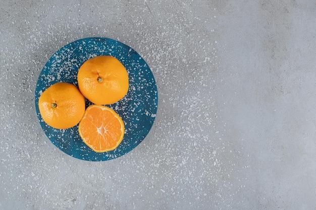 Plateau bleu recouvert de poudre de noix de coco avec des oranges sur une surface en marbre