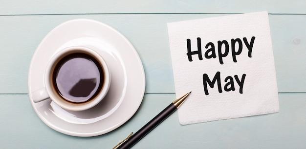 Sur un plateau en bois bleu clair, il y a une tasse de café blanche, une poignée et une serviette qui dit happy may