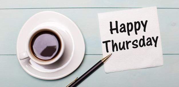 Sur un plateau en bois bleu clair, il y a une tasse de café blanche, une poignée et une serviette qui dit joyeux jeudi