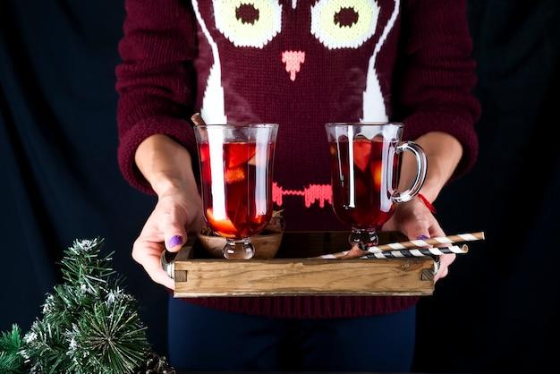 Plateau en bois avec du vin chaud fait maison avec des fruits et des épices dans des mains féminines sur un fond sombre