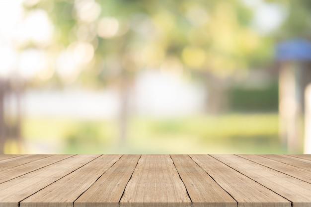 Plateau en bois sur fond flou au jardin pour le montage de vos produits