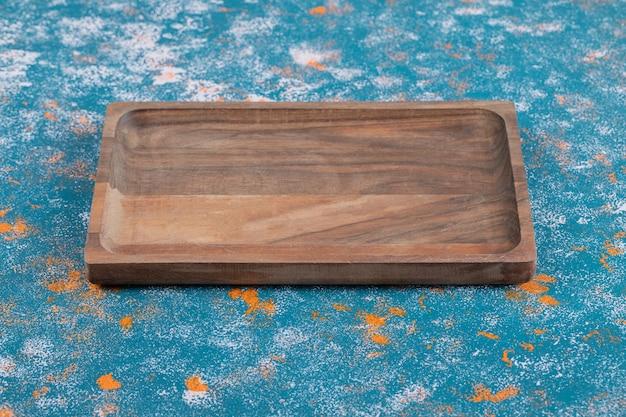 Plateau en bois isolé sur fond texturé