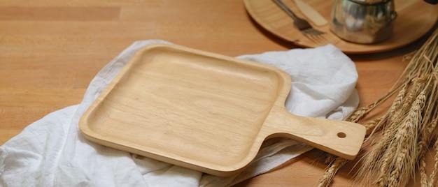 Plateau en bois maquette au-dessus de serviettes blanches sur table à manger en bois avec des décorations