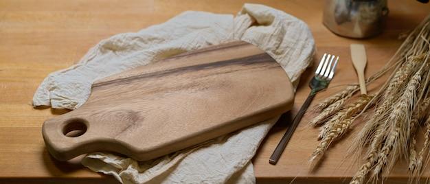 Plateau en bois maquette au-dessus de serviettes sur table à manger en bois avec fourchette et décorations en argent