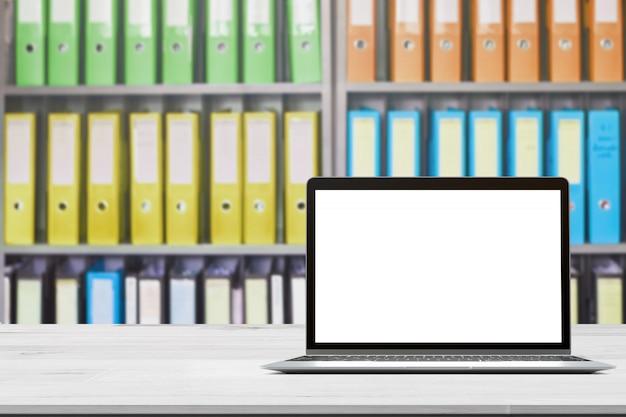 Plateau en bois avec ordinateur portable sur dossiers de documents de bureau flou debout dans une rangée de sur le stockage de documents pour le fond