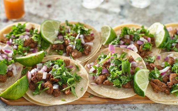Plateau en bois avec tacos carne asada sur tortilla de maïs