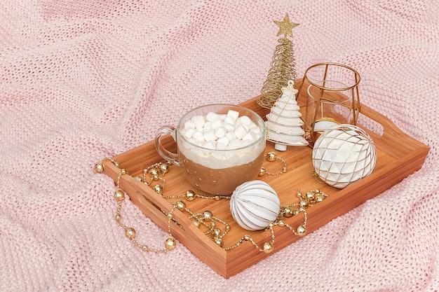 Plateau en bois avec tasse de cacao, guimauves et décorations de noël sur plaid rose chaud en tricot.