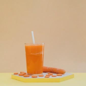 Plateau en bois avec des tranches de carotte et du jus