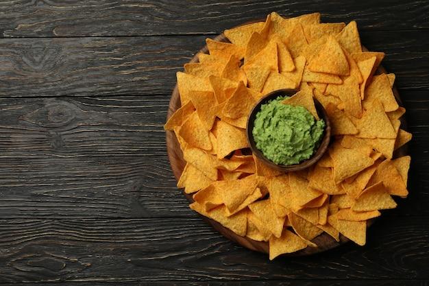 Plateau avec chips et bol de guacamole sur fond de bois, espace pour le texte