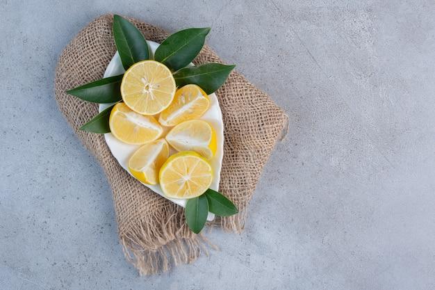 Un plateau de citrons tranchés sur un morceau de tissu sur fond de marbre.