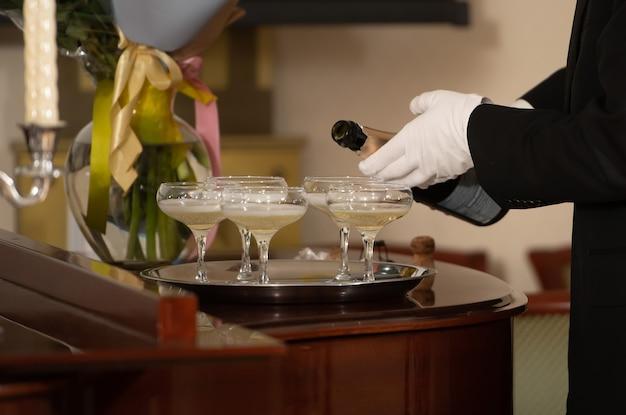 Un plateau avec des coupes de champagne et une bouteille de vin mousseux.