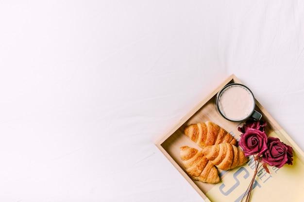 Plateau avec des croissants et des roses sur le lit