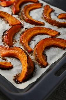 Plateau de cuisson avec citrouille au four sur fond texturé gris.