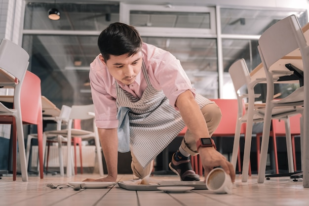 Plateau de dépose. jeune serveur inattentif portant un tablier rayé avec plateau de chute pour le client