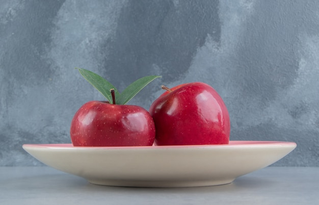 Un plateau avec deux pommes sur marbre.
