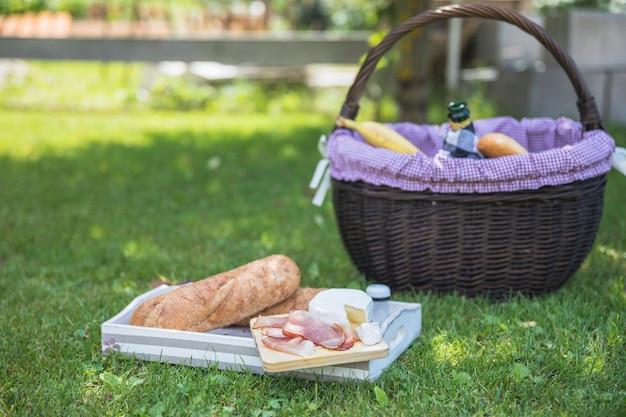 Plateau avec du pain; bacon; fromage et panier dans le parc