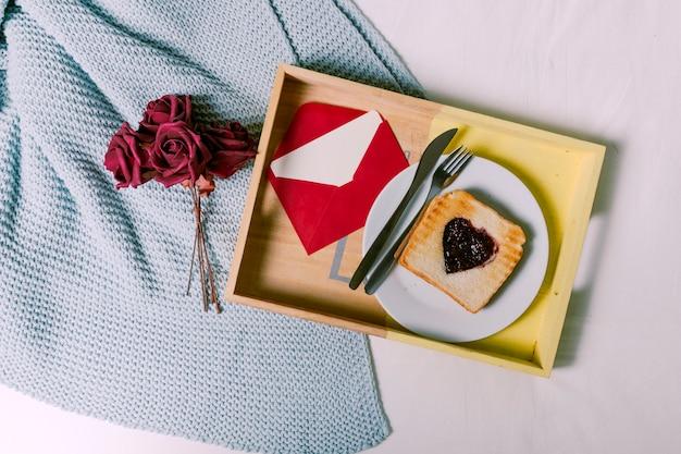 Plateau avec du pain grillé avec de la confiture en forme de coeur et enveloppe