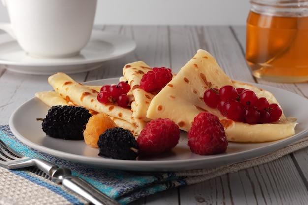 Sur un plateau, fines crêpes au miel, framboises, mûres et groseilles
