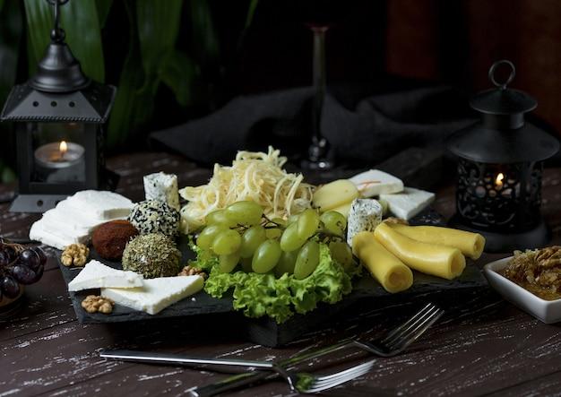 Plateau de fromages avec des bonbons, des noix et des raisins verts