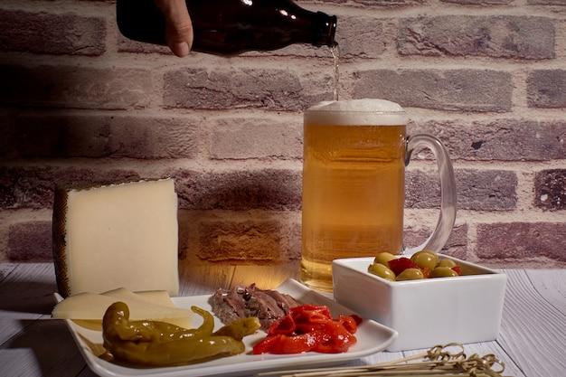 Plateau de fromages à côté d'une bière